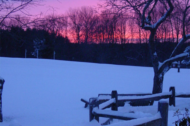 Snow covered fence and field at sunset