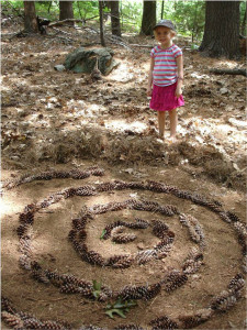 Camper creating landscape art with pine cones and other natural materials