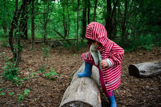 Child stepping over log