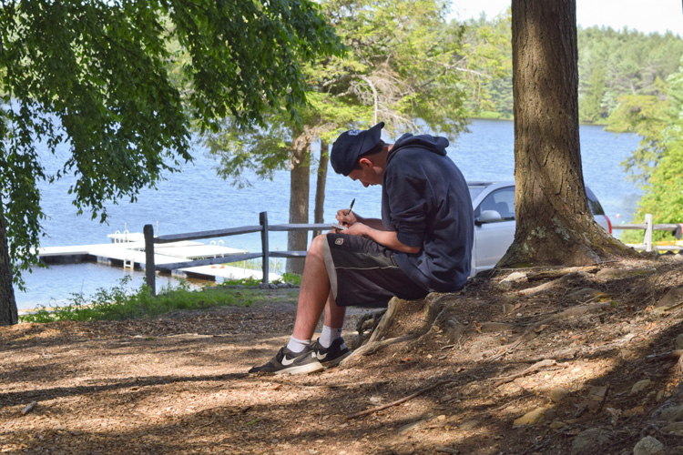 A counselor enjoys some quiet reflection and journaling by Hubbard Pond.