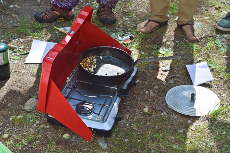 A near-empty pot of fresh popcorn on a camp stove resting on the ground.
