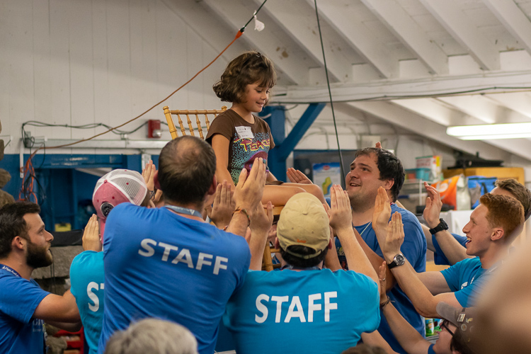 Camp staff lift a girl in a chair to sing and celebrate her birthday