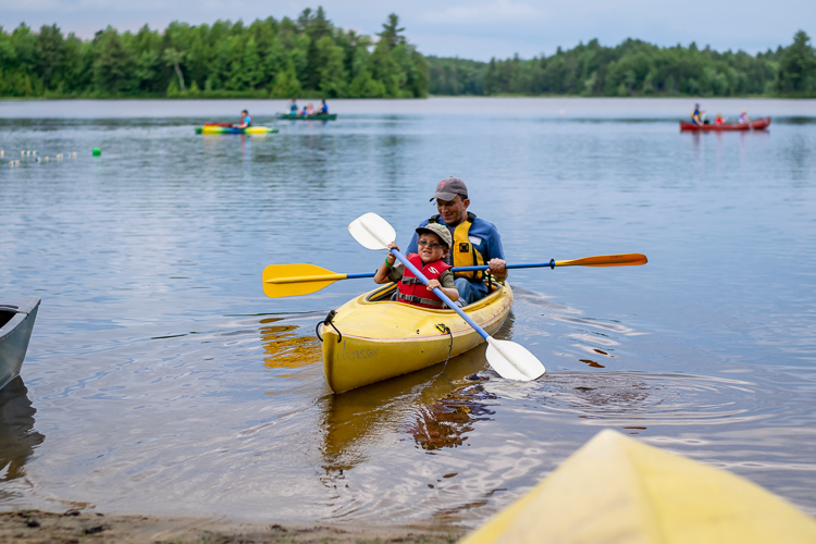Father and son launch a two-person kayak on Hubbard Pond