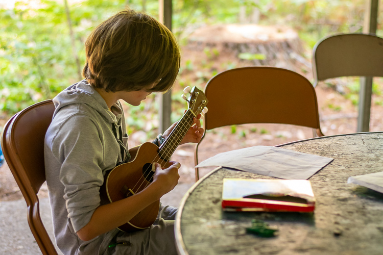 A camper plays the ukulele in the Arts & Crafts building