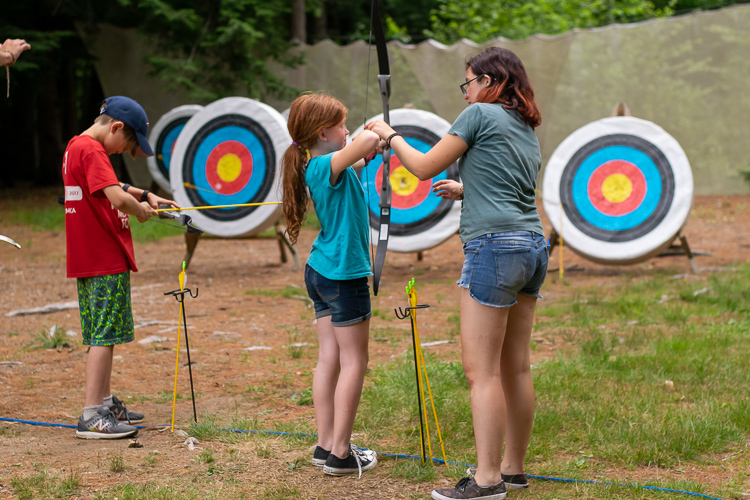 Grace helping a camper try out archery
