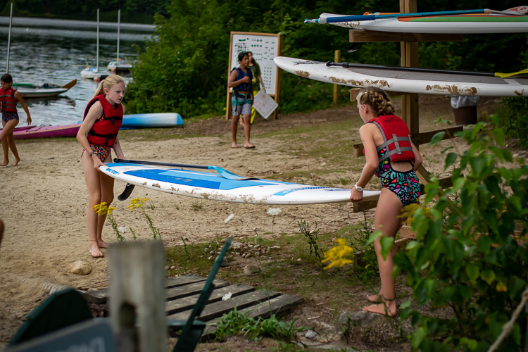 Two campers help each other bring a paddleboard to the water