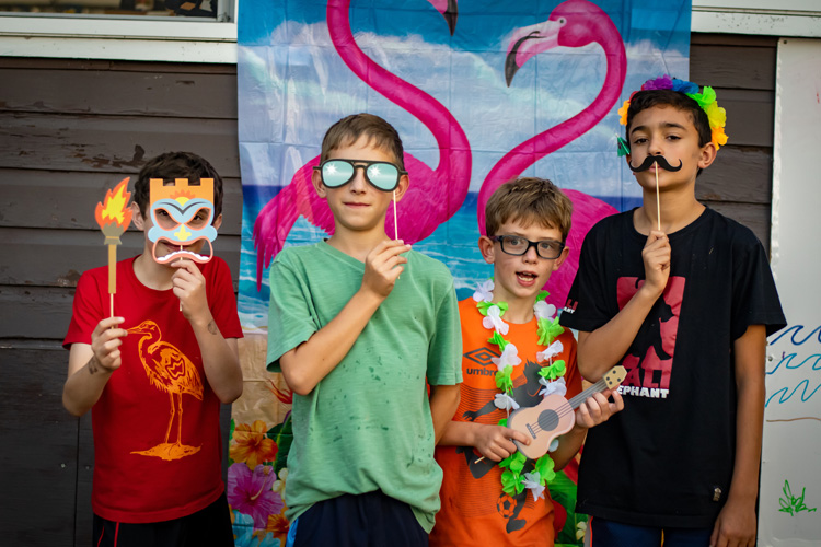 Campers pose with props for a photo booth