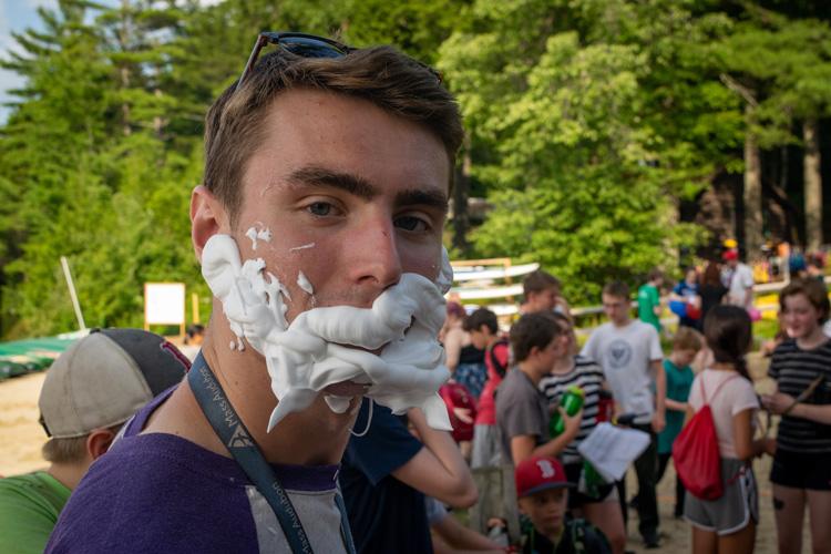 Dustin Ledgard leading a silly Camp Olympics activity involving shaving cream