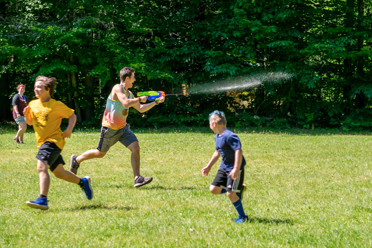 Jackson Lieb playing a game of tag with campers on a hot day using a super soaker