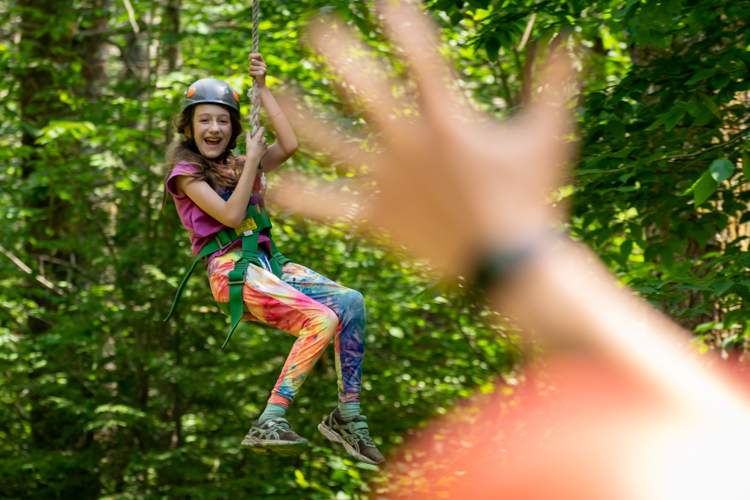 A camper enjoying the zipline on our ropes course