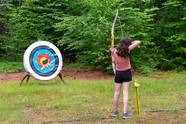 A camper practicing at the archery range