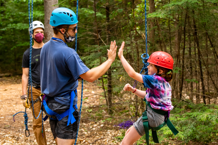 Ropes Course leader Sam gives a camper a high five after she tackled a big challenge on the ropes course
