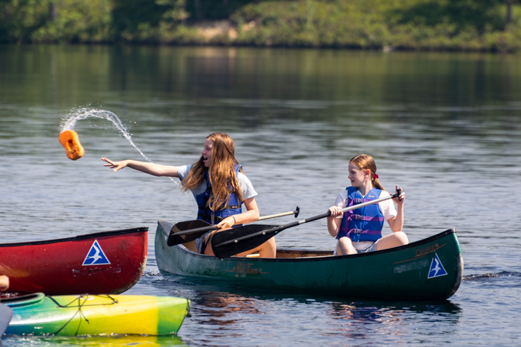 Playing a game in the kayaks and canoes involving a wet sponge and a lot of laughter