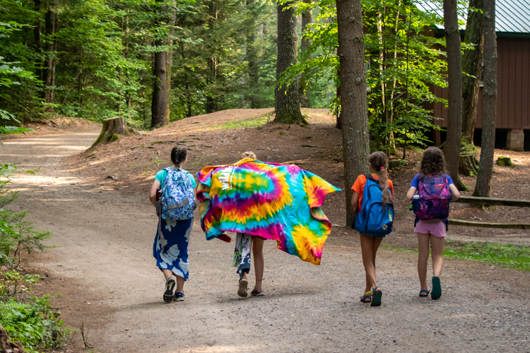 Four campers walking down the road, one carrying a tie-dyed Wildwood blanket