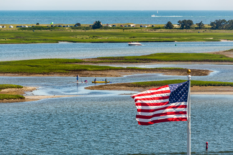 The American flag flies in the foreground over a tidal flat with kayakers in the mid-ground and the ocean in the background.