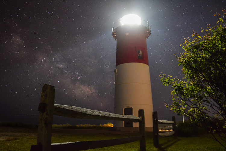 Starry sky behind an illuminated lighthouse