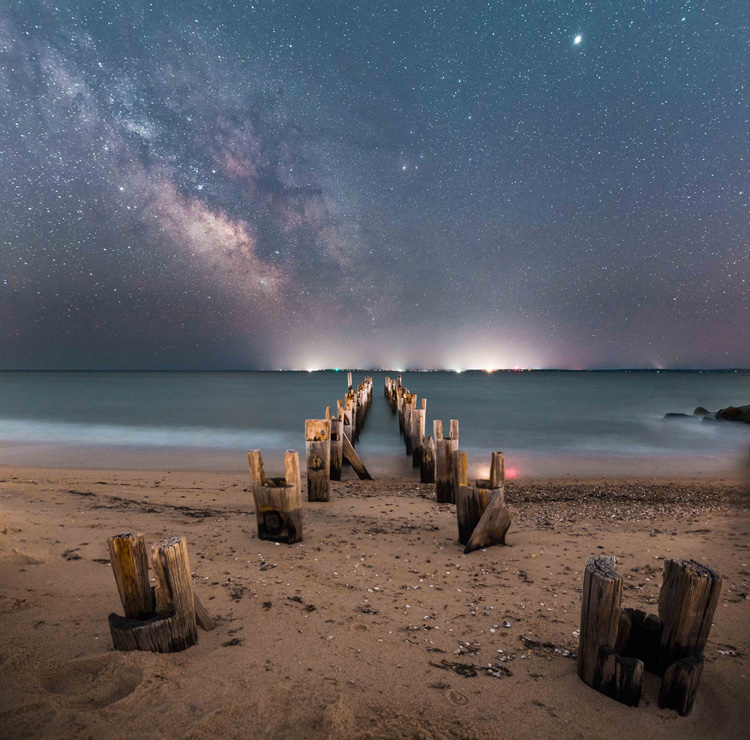 Starry sky over an old jetty on the beach