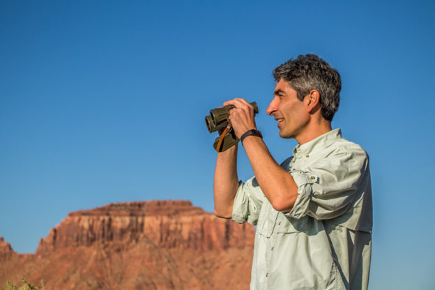 Flavio Sutti holding binoculars at Arches National Park in Utah