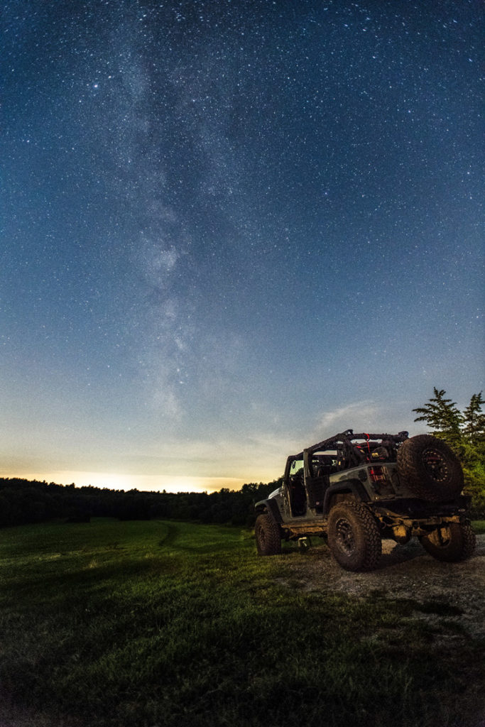 A jeep parked on a dirt road by a meadow with a star-filled sky above