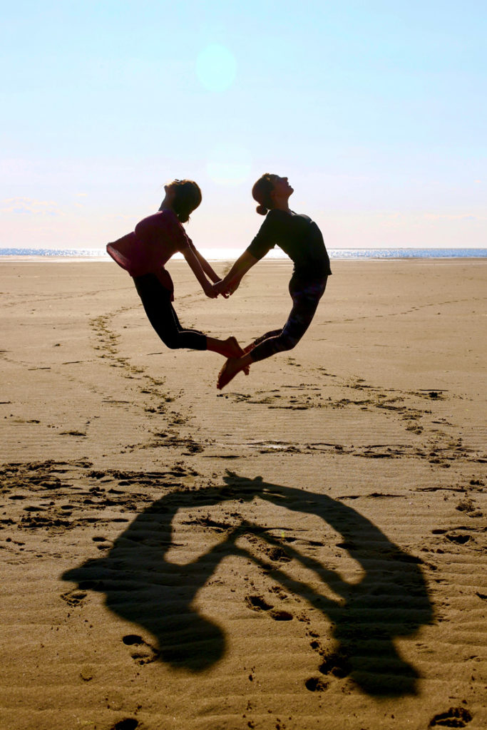 Two women jumping in mid-air, forming a heart shape at the beach © Debra Grossbaum