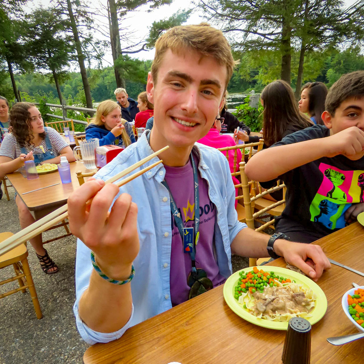Dustin Ledgard enjoying an outdoor lunch at Wildwood with chopsticks