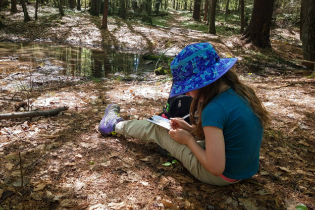 Willow writing in her nature journal beside a vernal pool at Arcadia