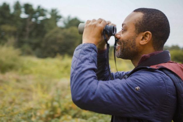 A Black man looking through a pair of binoculars at a wildlife sanctuary